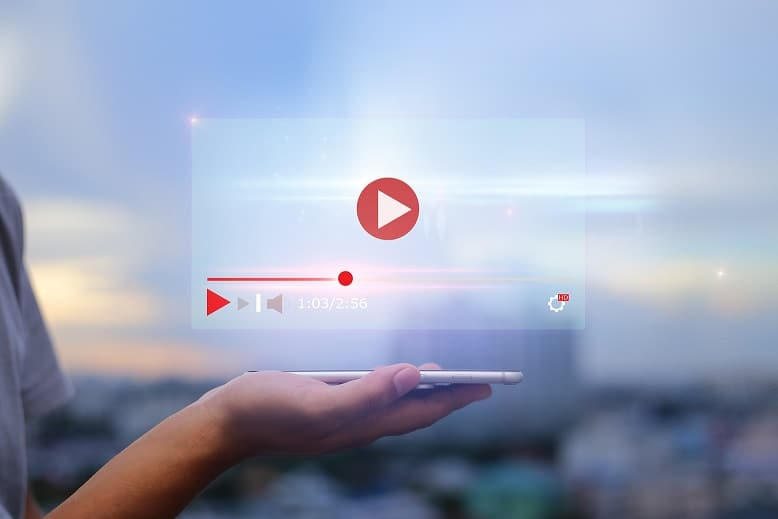 live video content online streaming marketing concept.Hands holding mobile phone on blurred urban city as background